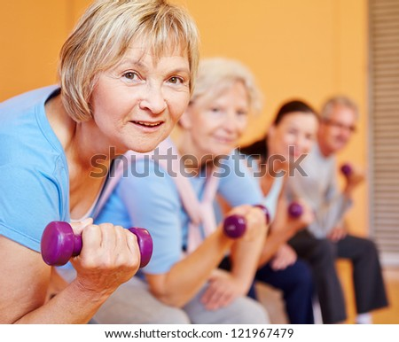 Senior woman with dumbbells doing back training in a fitness center - stock photo
