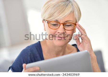 Senior woman with eyeglasses browsing on digital tablet - stock photo