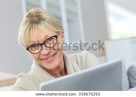 Senior woman with eyeglasses using digital tablet at home - stock photo