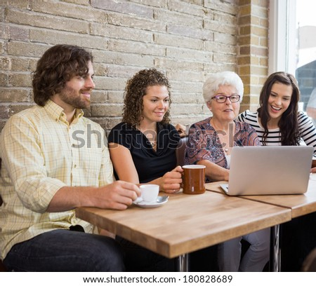 Senior woman with friends using laptop at table in cafe - stock photo