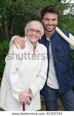 Senior woman with gardener - stock photo