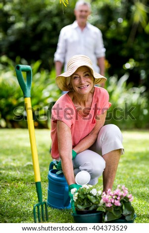 Senior woman with gardening equipment against man in yard - stock photo