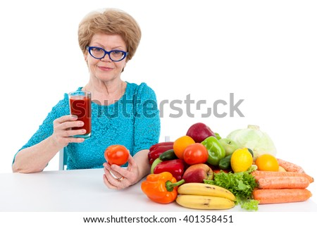 Senior woman with glass of juice and tomato in her hands sitting at table with fruits and vegetables, isolated on white background - stock photo