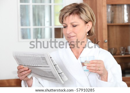 Senior woman with glass of water and newspaper - stock photo