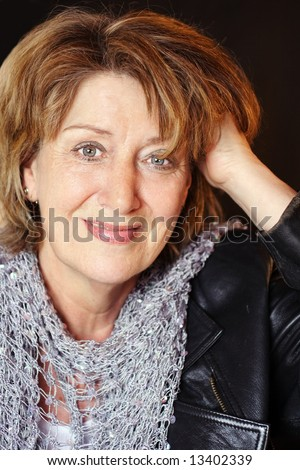 Senior woman with hand in hair and leather jacket - stock photo