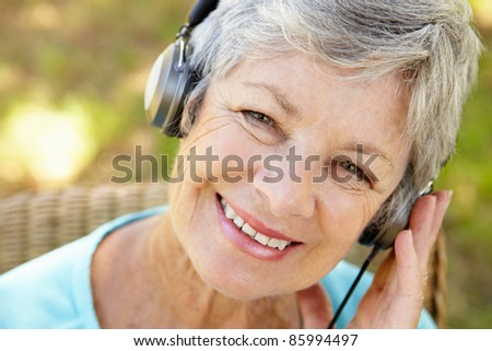 Senior woman with headphone - stock photo