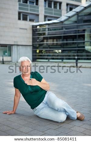 Senior woman with heart attack sitting on sidewalk - stock photo
