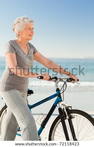 Senior woman with her bike - stock photo