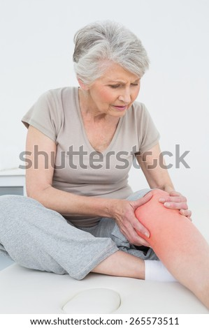 Senior woman with her hands on a painful knee while sitting on examination table - stock photo