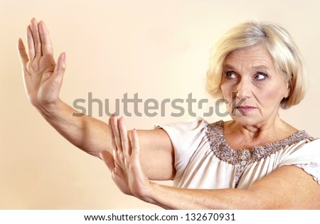 senior woman with her hands signaling to stop over light background - stock photo