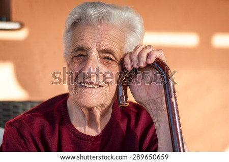 Senior woman with her stick - stock photo