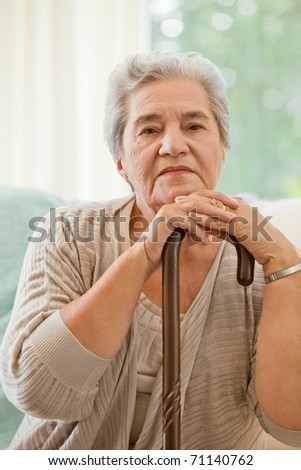 Senior woman with her walking stick - stock photo