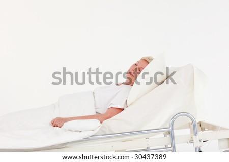 Senior woman with illness in hospital - stock photo