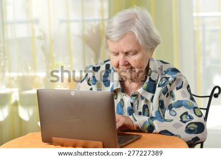 Senior woman with laptop in her room. MANY OTHER PHOTOS FROM THIS SERIES IN MY PORTFOLIO. - stock photo