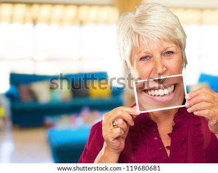 Senior Woman With Magnifying Glass Showing Teeth, Indoor - stock photo