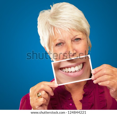 Senior Woman With Magnifying Glass Showing Teeth On Blue Background - stock photo