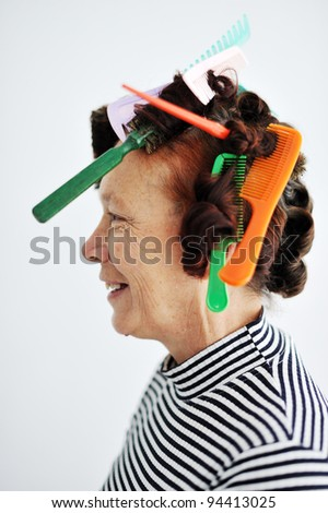 Senior woman with many combs on hair - stock photo