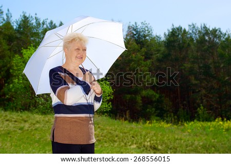Senior woman with parasol in forest - stock photo