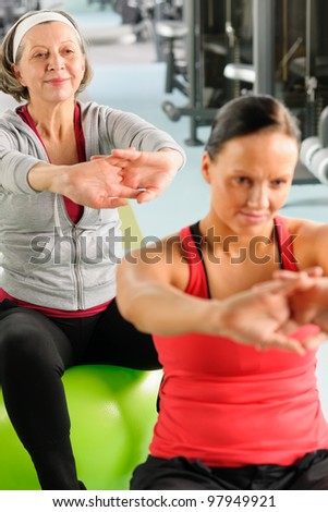 Senior woman with personal fitness trainer stretch out at gym - stock photo