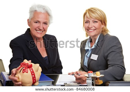 Senior woman with piggy bank and financial adviser in office - stock photo