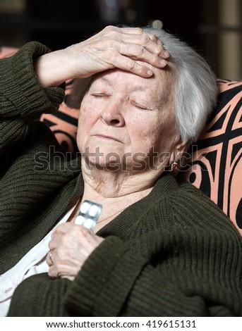 Senior woman with pills at home. Headache - stock photo