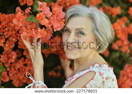 Senior woman with red flowers at nature - stock photo