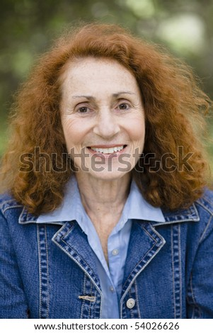 Senior Woman With Red Hair Smiling Directly To Camera - stock photo