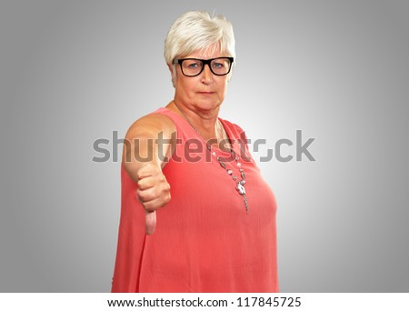 Senior Woman With Thumbs Down Isolated On gray Background - stock photo