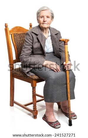 Senior woman with walking stick sitting on chair over white background  - stock photo