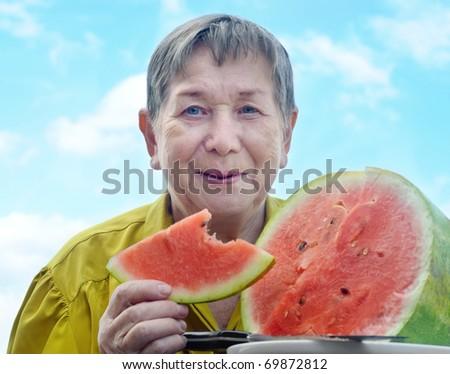Senior woman with watermelon - stock photo