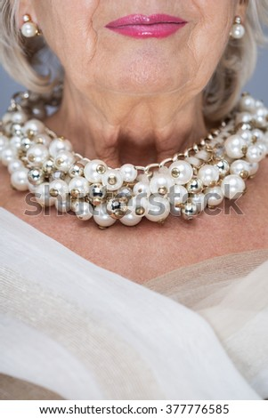 Senior woman with white shawl, pearl earrings and necklace