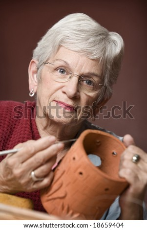 Senior woman working on a clay sculpture - stock photo