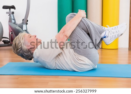 Senior woman working on exercise mat in fitness studio - stock photo