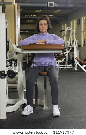 Senior woman working out in gym - stock photo