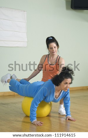 Senior woman working out with her personal trainer - stock photo