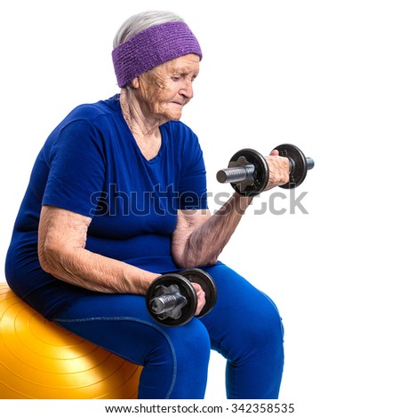 Senior woman working out with with dumbbells while sitting on fitball - stock photo