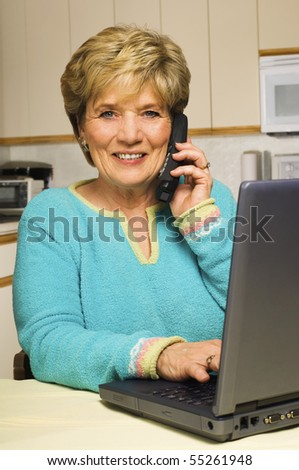 Senior woman works from home; talks on phone and uses laptop.