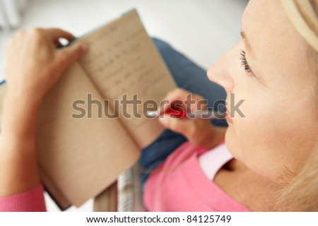 Senior woman writing in notebook - stock photo