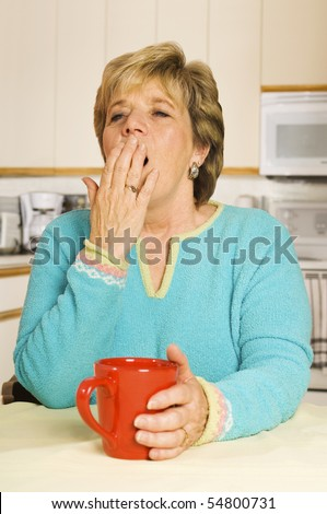 Senior woman yawns while sitting at her kitchen table with a coffee mug - stock photo