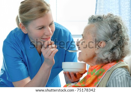 senior woman 90 years old being fed by a nurse - stock photo