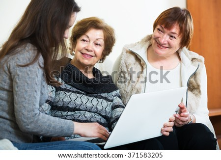 Senior women and young girl with laptop in home interior