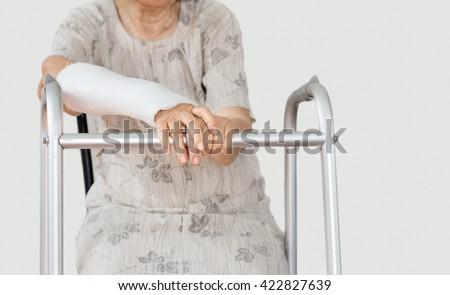 Senior women broken wrist using walker. - stock photo