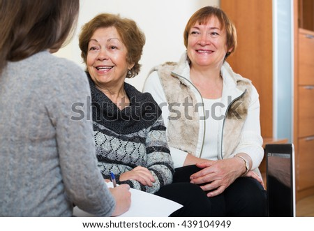 Senior women consulting with banking agent and smiling at home. Focus on central person  - stock photo