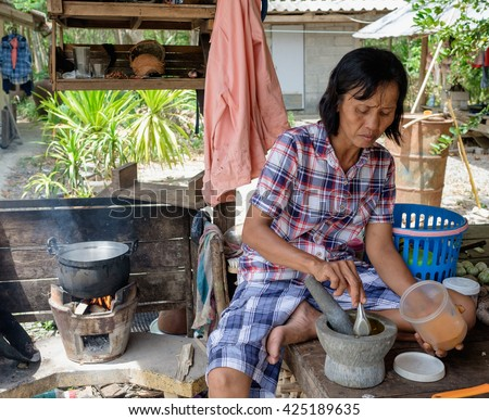 Senior women cooking outdoor, Thai countryside and local lifestyle, mother cook sitting in hut with pot and firing firewood in stove - stock photo