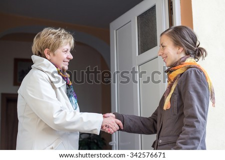 Senior women greeting young girl in the doorway - stock photo