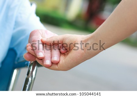 Senior women in wheelchair holding hands with caretaker - stock photo