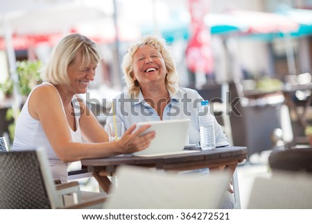 Senior women laughing while using tablet PC in cafe - stock photo