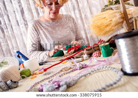 Senior women sews by hand and making owl shape ornament.