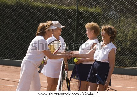 Senior women shaking hand after tennis match - stock photo