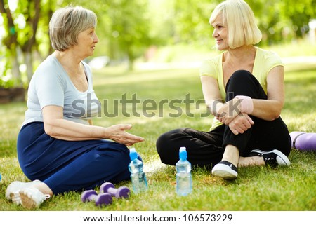 Senior women sitting on the grass and talking after a workout - stock photo
